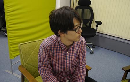 座って左を向くプログラマの松村さん